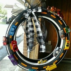 "Paint a road, hot glue little cars onto an old tire, and add a black & white checkered bow-- great ""wreath"" for a little boy's room!"