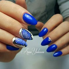 Ravenous blue butterfly nail art design. The fierce looking design is absolutely amazing as it looks powerful in electric blue polish with the contrasting white background to highlight the butterfly design.