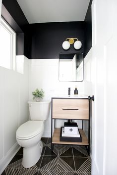 Black + White Powder Room Makeover Powder room makeover with a wood vanity. A powder room makeover with white board and batten and black paint. Love the gold light fixture, wood vanity, and other details in this small bathroom makeover! Black White Bathrooms, Bathroom Black, Bathroom Canvas, Parisian Bathroom, Black White Rooms, Small Bathroom Paint, Remodled Bathrooms, Bathroom Things, White Bathroom Accessories