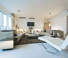 Home Theater planejado com decoração contemporânea. Sala de TV. Móveis elegantes, tons neutros e poltrona Barcelona de Mies van der Rohe.