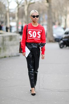 Vanessa Hong fashion blogger at The Haute Pursuit wears a red top with the inscription 'SOS' and black vinyl pants outside the Paco Rabanne show...