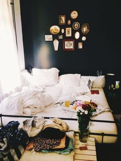 Black in the bedroom contrasts well with white sheets, flowers, and some vintage photos.