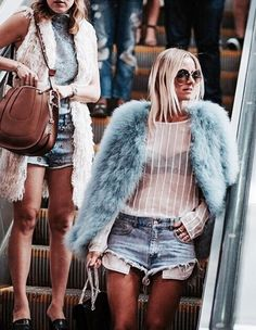 Pale blue fur jacket with pale pink see-through sweater with black bra, and blue denim shorts