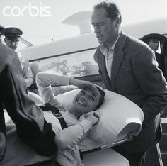 Actress Audrey Hepburn, who broke her back while riding a horse on location in Mexico, laughs happily on her arrival here with her husband, actor Mel Ferrer. Miss Hepburn was strapped onto her...