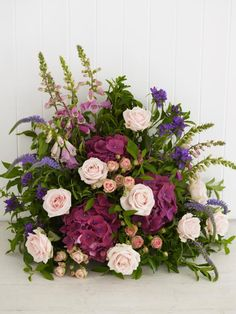 Arranging hydrangeas, veronicas, roses and foxgloves punctuate forsythia foliage somewhat randomly demonstrates how a structured, traditional front-facing arrangement often looks better with an informal style.