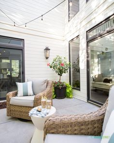 An outdoor courtyard patio with natural woven chairs, white concrete side tables, planter filled with hibiscus and other plants, string lights and more! Indoor Outdoor Rugs, Outdoor Spaces, Outdoor Chairs, Outdoor Living, Outdoor Decor, Concrete Outdoor Table, Evening Garden Parties, Patio String Lights, Woven Chair