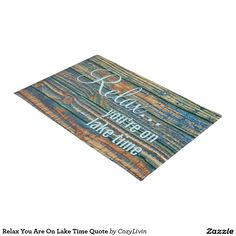 """Relax You Are On Lake Time Quote Doormat. Decorative and trendy design on a stylish and fun door mat. Blue, brown and yellow green colored wooden planks pattern with """"Relax... you're on lake time"""" quote. Cute design for the artistic interior designer and motivational or inspirational quotes lover. Original and modern home decor product for those looking to decorate their home entrance outside space, or front porch of their beach house, country cottage, log cabin, lake or river vacation home."""