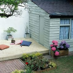 Mint green shed with bright flowers and platform deck. More stylish she sheds at http://www.redonline.co.uk
