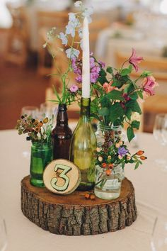 Brown and green bottles on slabs of wooden tree stumps as table centre pieces with glass jars filled with wild flowers - Image by LM Weddings Photography