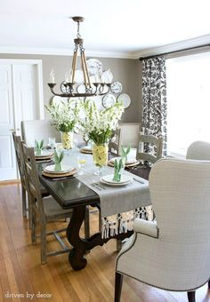 Dining room with simple Easter table decorations - floral centerpieces in vases lined with lemon slices and bunny ear napkins