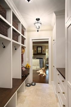 Awesome mudroom with limestone tiled floors and built-in cubbies with benches for each family member. Opposite the cubbies, are storage cupboards and drawers with brass hardware and a stained wood countertop. Tan colored walls finish the room lit by a pair of Hundi lanterns.