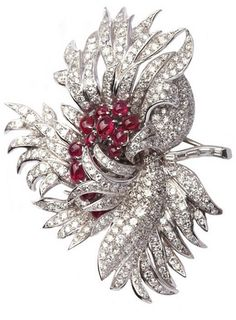 *A magnificent brooch manufactured by Van Cleef & Arpels during the 1950s, representing a a sophistically articulated dahlia flower. The item presents approximately 18cts of brilliant and baguette cut diamonds enriched by 5cts of cabochon rubies in the central element of the brooch. Mounting is in platinum.