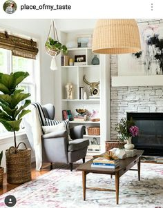 cozy living room with fireplace, fiddle leaf fig, and rattan woven lighting.