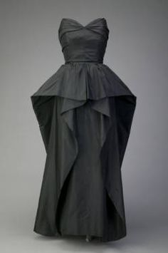 Evening dress, ca. 1948. Silk taffeta. Christian Dior.  Dress of black silk taffeta. Strapless fitted bodice with sweetheart neckline and low-cut back. Natural waist. Long peplum covers hips in front; longer in back. Front of skirt has zigzag panels on each side that are created by turning the fabric back on itself. Floor-length underskirt.
