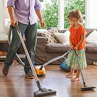 father and child vacuuming