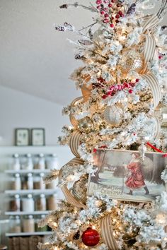 Love this flocked Christmas tree with red ornaments, vintage santa, and the striped ribbon cascading down.