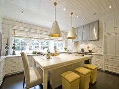 We're loving everything about this Atlanta kitchen. The bright white cabinets, counter tops, and island; the pendant and spot lighting; the open shelving. Are those #lucite pulls!? This one got it right! #coastdesign