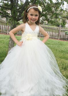 Girls Tutu dress Flower Girl Gown www.sugarbabybow.com $65.00 and up Dress has a satin bodice halter top with satin ribbons attached. Ribbons can be tied at the neck or criss crossed and looped through back of the dress, then tied.  Dress has a permanently sewn satin slip inside to prevent itchiness and for the dress being see through. Dress has a rhinestone flower on the waist band. Headband sold seperately. Dress can be customized in any color. Email me for inquiries.
