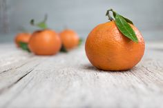 tangerine mandarine clementine - Fresh orange clementine from Spain with a green leaf on a rustic white wooden table.