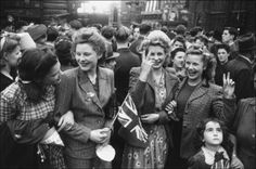 An ecstatic group of girls celebrating news of Germany's surrender in the streets of London.