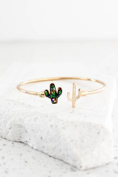 This open ended bracelet features a cactus on both ends. The bulk of this bracelet is done in a gold high polish finish, as well as one of the cactus'. The other cactus is decorated in a mix of blue,
