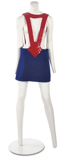 PIERRE CARDIN (B.1922)  A PINAFORE SKIRT  circa 1970, the straps of scarlet glossy vinyl with quilting, the skirt of navy wool jersey, with designer's label Pierre Cardin, Paris, New York