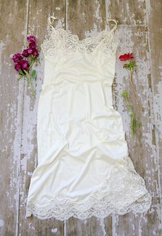 Lifted Veil Slip Dress  Price: $58.00  A gorgeous vintage full slip dress, perfect for the soon to be bride or newlywed! White silky slip with lots of lace and floral embroidery throughout. Scalloped lace on bust and hem.