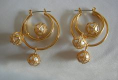 Beautiful hoop earrings for pierced ears. Gold tone setting holds clusters of faux pearls. This striking set measures about 1 1/2 in diameter. In