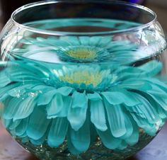 Glass marbles at the bottom of a fish bowl with a giant daisy! Make sure to use distilled water so there aren't any floaters. You can also put tea lights to float on top.