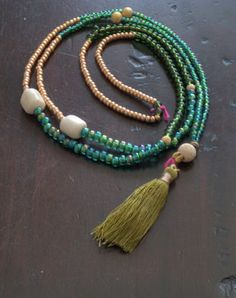 Beaded Tassel necklace in Green tones with 18 k gold stardust balls and bone Materials: beads, bone, gold, stardus balls, olive green tassel, brass, string