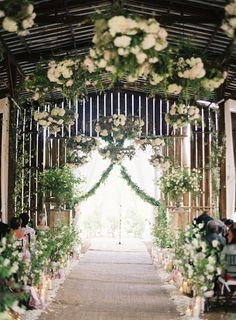 Lush rose and greenery garlands ornate this beautiful wedding aisle