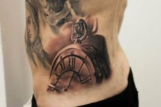An incredible tattoo done on the hip and abdomen of a young man. This is a pocket watch with Roman numerals. The work has a soft copper color for an