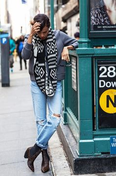 Distressed jeans and cowboy boots are worn with a gray jacket and a printed infinity scarf.
