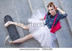 Girl listening to music on headphones. Funny hipster ballerina sitting on the stairs. A girl wearing a tutu, ballet shoes and sneakers, sunglasses. The girl is sitting on a skateboard. Youth fashion.