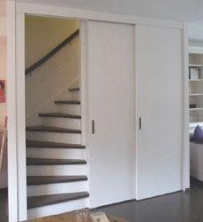 schuifdeur voor trap geopend en opbergruimte aan de andere kant