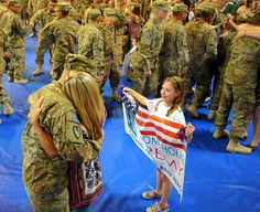 Specialist Jeremy Hudson hugs his wife as his ten-year-old daughter Averie holds a welcome home sign on March 12 as he and other soldiers from the 530th Engineer Company arrive at Fort Stewart in Georgia. -- PhotoBlog - Troops welcomed home from Afghanistan