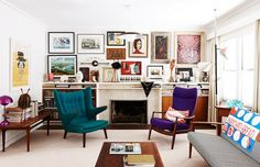 Sitting area with jewel tone armchairs and gallery wall of art