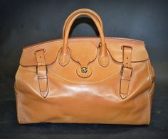 Ralph Lauren Bag crafted in Italy, fom luxurious Calf skin, and finished with polished lock, with leather closure,with a functioning logo embossed brass cooper lock.leather straps extended through openings in the top , and are secured with buckled closures.two leather handles.:removable leather shoulder strap and key pouch.:twill lined interior with a large interior pouch pocket at one side, a side zip pocket, on the other hardware reinforced base:elegantly presented in a protective logo…