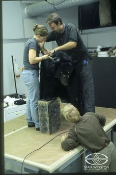 Richard Landon and fabrication artist Amy Whetsel fit John Rosengrant into a bear suit with animatronic facial features.