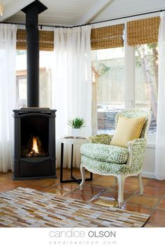 Nothing says cozy like a gas-burning wood stove, comfortable chair and a good book! Terra Cotta tile Floors • Woven Wood Blinds • Modern Farmhouse Sunroom • #candiceolson #candiceolsondesign Wood Blinds, Fireplace Design, Terra Cotta, Sunroom, Vignettes, Modern Farmhouse, Stove, Floors, Beautiful Homes