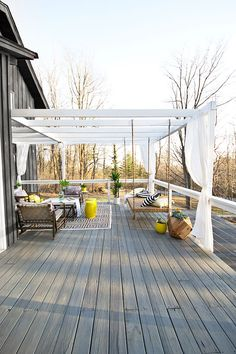 A backyard deck with a pergola, privacy curtains and a hanging bench