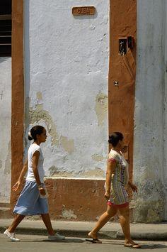 Two Cuban ladies walking down Cuba Calle in Havana, Republic of Cuba…