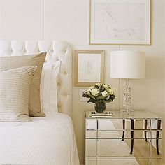 Simply beautiful chic bedroom. White cream silk tufted headboard with linen throw pillows! Mirrored nightstands with crystal lamps and art! Love this vignette! White elegant bedroom. White paint wall color!