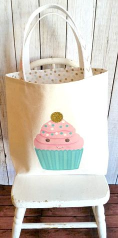 Handmade canvas tote with gold glittery dots,mint green dots and pink dots lining the bag ! Pink and gold chevron ribbon adorn the webbing handles.Original Artwork on the front of an adorable happy face cupcake with a glittery gold dot on top! The design is heat pressed with a vintage look. Made for your little one to tote all their things and we know they have plenty of those! Made of a durable canvas to withstand lots of play.  Sweet birthday gift bag for that dear little girl!  Childs…