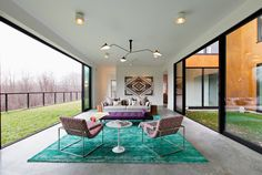 The living room is equipped with sliding glass doors on two sides, which open it wide to the outdoors. On the left is a grassy green roof; on the right is a courtyard with artificial turf. The vintage chairs are by Milo Baughman, and the rug is from Land of Nod. (Photo: Preston Schlebusch for The New York Times)