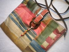 """9""""x 8 1/2"""" hand-sewn purse made with all reused and recycled materials: multi-coloured print cotton, brown and gold upholstery lining, leather shoulder strap, wood latch and beads, beige cotton hand stitching $15.00, 10% of all proceeds go to Syringomyelia research and chronic pain support in Canada. Click picture for ordering details. pursesbysharon.blogspot.ca"""