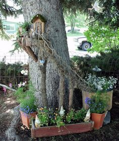 Use an tree trunk to create a wonderful fairy garden scene like this one with flowers and a staircase going to a door upstairs.