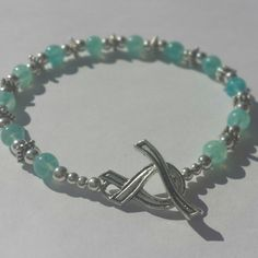 Sexual Violence Awareness Bracelet with Ribbon Toggle Clasp Part of the S & K Awareness Line. Teal glass beads with silver spacer beads and a silver awareness ribbon toggle clasp.