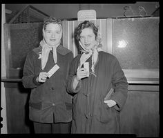 Two unknown young women displaying their tickets to a game in front of a ticket window at Fenway Park.1940 - 1949 (approximate)