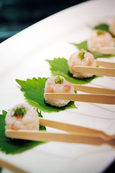Rice and shrimp wontons topped with a garnish are served with natural wooden tongs.///www.annmeyersignatureevents.com